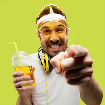 シャツを着た若い男のハーフレングスのクローズアップの肖像画。ヘッドフォンと飲み物を持つ男性モデル。人間の感情、表情、夏、週末のコンセプト。指差しと笑顔。