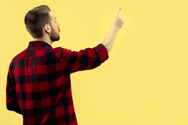 黄色のスペースにシャツを着た若い男の肖像画の半分のクローズアップ。人間の感情、表情のコンセプト。正面図。トレンディな色。ネガティブスペース