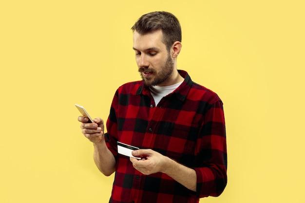 절반 길이 노란색 공간에 셔츠에 젊은 남자의 초상화를 닫습니다. 인간의 감정, 표정 개념. 전면보기. 트렌디 한 색상. 부정적인 공간