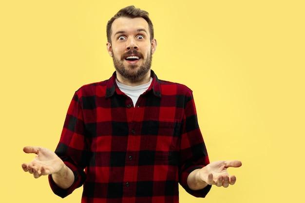 Поясной крупным планом портрет молодого человека в рубашке на желтом пространстве