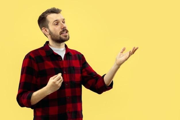 黄色のシャツを着た若い男の肖像画の半分のクローズアップ