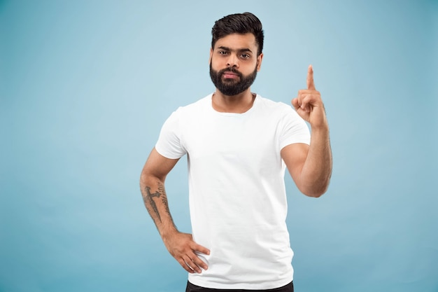 Поясной крупным планом портрет молодого человека в белой рубашке на синем