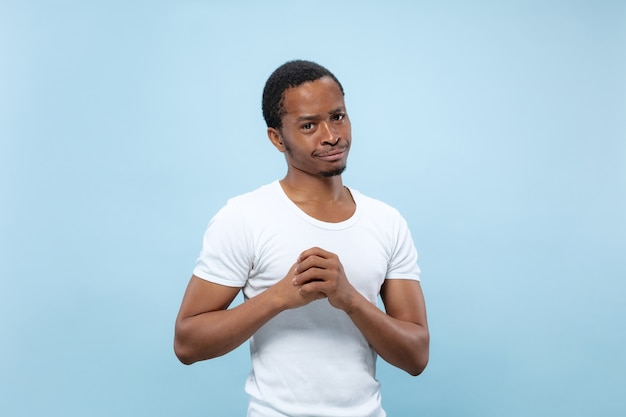Half-length close up portrait of young african-american male model in white shirt on blue wall. human emotions, facial expression, ad concept. doubts, asking, showing uncertainty, thoughtful.