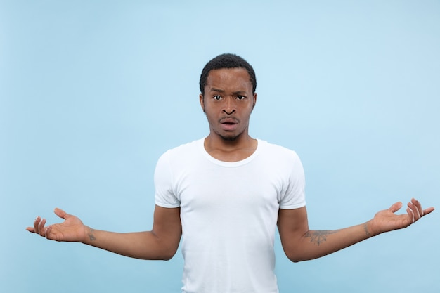Half-length close up portrait of young african-american man in white shirt on blue background. human emotions, facial expression, ad concept. asking and uncertain, doubts, negative emotions.