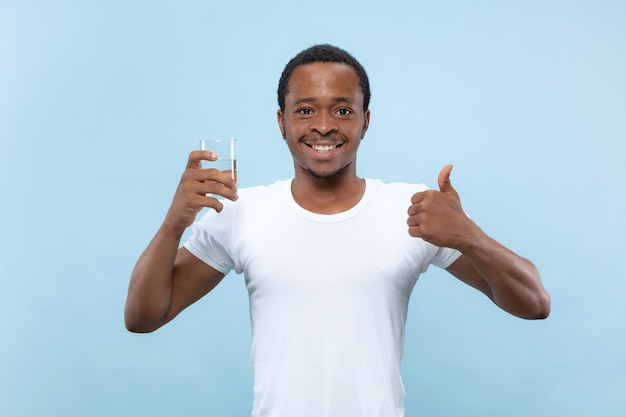 Half-length close up portrait of young african-american man in white shirt on blue background. human emotions, facial expression, ad concept. holding a glass and drinking water.