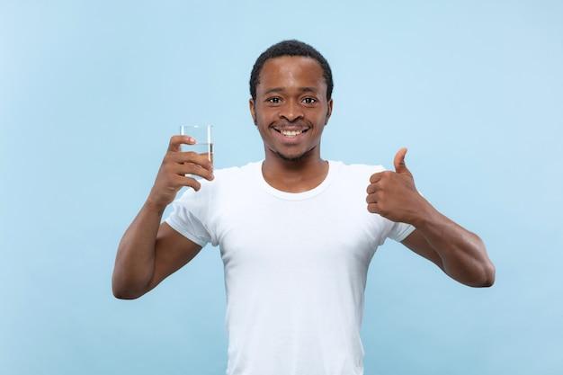 Ritratto alto vicino a mezzo busto di giovane uomo afro-americano in camicia bianca su sfondo blu. emozioni umane, espressione facciale, concetto di annuncio. tenendo un bicchiere e acqua potabile.