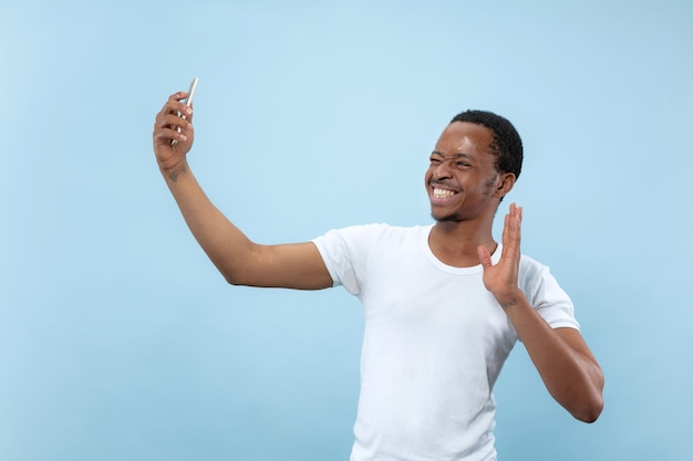 Half-length close up portrait of young african-american man in white shirt on blue background. human emotions, facial expression, ad concept. making selfie or content for social media, vlog.
