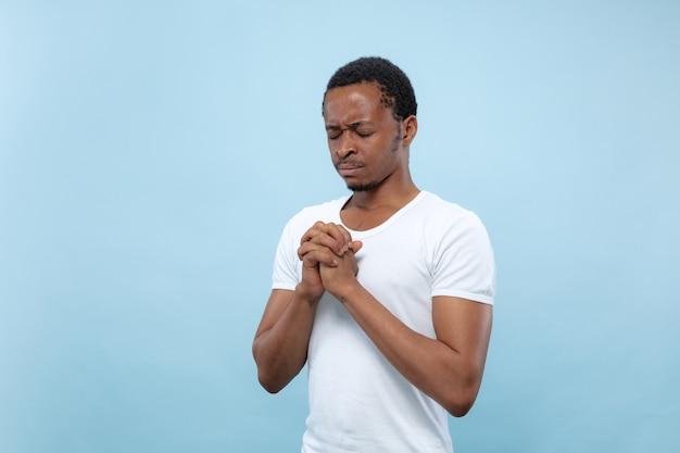 Ritratto alto vicino a mezzo busto di giovane uomo afro-americano in camicia bianca su sfondo blu. emozioni umane, espressione facciale, concetto di annuncio. pregare con gli occhi chiusi, sembra speranzoso.