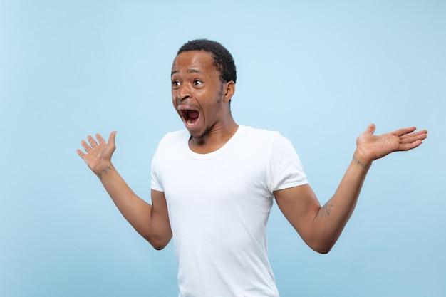 Ritratto alto vicino a mezzo busto di giovane uomo afro-americano in camicia bianca su sfondo blu. emozioni umane, espressione facciale, annuncio, concetto di vendita. invitante, sembra scioccato e stupito. copyspace.