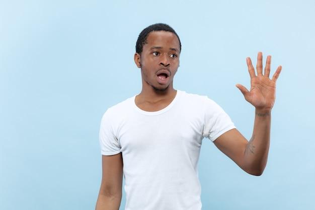 Ritratto alto vicino a mezzo busto di giovane uomo afro-americano in camicia bianca su sfondo blu. emozioni umane, espressione facciale, annuncio, concetto di vendita. incontrare qualcuno, salutare, invitare.