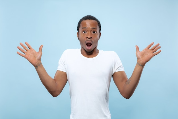 Half-length close up portrait of young african-american man in white shirt on blue space. human emotions, facial expression, ad, sales concept. inviting, looks shocked and astonished
