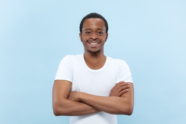Half-length close up portrait of young african-american man in white shirt on blue space