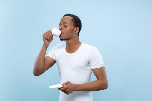 Ritratto alto vicino a mezzo busto di giovane uomo afro-americano in camicia bianca su spazio blu.