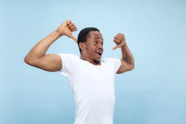 Ritratto alto vicino a mezzo busto di giovane uomo afro-americano in camicia bianca sulla parete blu. emozioni umane, espressione facciale, annuncio, concetto. celebrando, meravigliato, stupito, scioccato, pazzo felice.