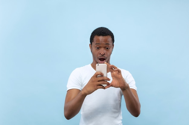 Half-length close up portrait of young african-american man in white shirt on blue wall. human emotions, facial expression, ad concept. taking a photo or vlog content on his smartphone.