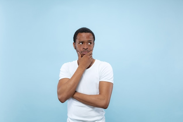 Half-length close up portrait of young african-american man in white shirt on blue wall. human emotions, facial expression, ad concept. thoughtful, thinking covering face with his hands.