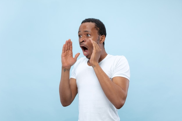 Half-length close up portrait of young african-american man in white shirt on blue wall. human emotions, facial expression, ad, sales, concept. screaming, calling for somebody, announces.