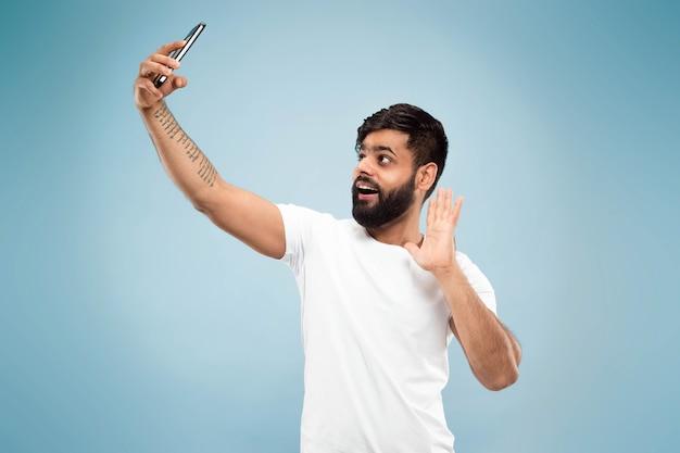Ritratto alto vicino a mezzo busto di giovane uomo indù in camicia bianca su sfondo blu. emozioni umane, espressione facciale, concetto di annuncio. spazio negativo. fare selfie o videoblog, vlog, chat.