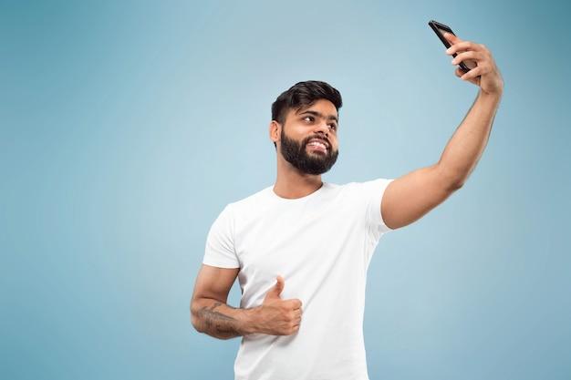 Mezzo busto vicino ritratto di giovane uomo indù in camicia bianca su sfondo blu. emozioni umane, espressione facciale, concetto di annuncio. spazio negativo. fare selfie o videoblog, vlog, chat.