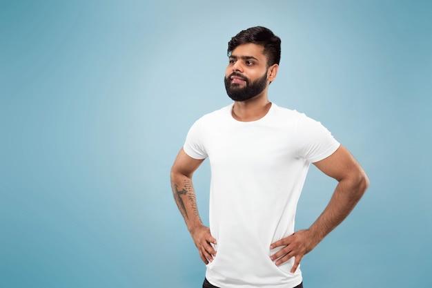 Mezzo busto vicino ritratto di giovane uomo indù in camicia bianca su sfondo blu. emozioni umane, espressione facciale, concetto di annuncio. spazio negativo. in posa, in piedi e sorridente, sembra calmo.