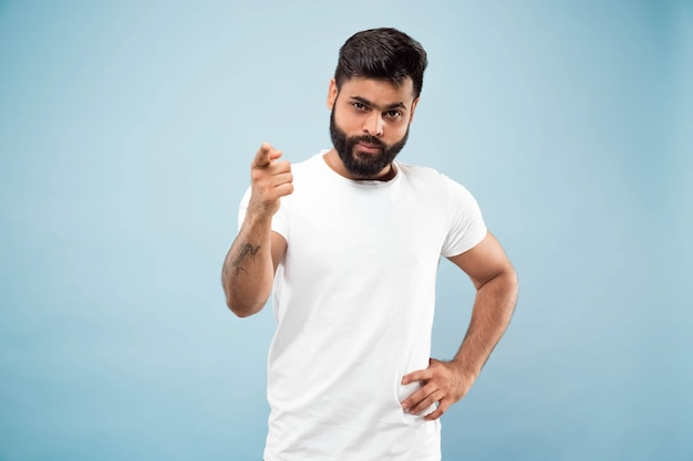 Mezzo busto vicino ritratto di giovane uomo indù in camicia bianca su sfondo blu. emozioni umane, espressione facciale, concetto di annuncio. spazio negativo. mostrare barra vuota, indicare, scegliere, invitare.