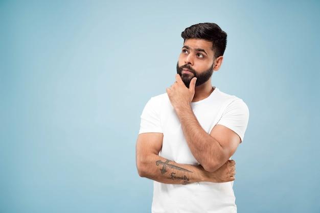 Mezzo busto vicino ritratto di giovane uomo indù in camicia bianca su sfondo blu. emozioni umane, espressione facciale, concetto di annuncio. spazio negativo. pensando tenendo la mano sulla barba. scegliere.
