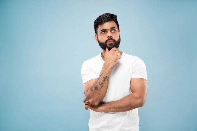 Half-length close up portrait of young hindoo man in white shirt on blue background. human emotions, facial expression, ad concept. negative space. thinking while holding hand on his beard. choosing.