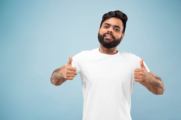 Half-length close up portrait of young hindoo man in white shirt on blue wall. human emotions, facial expression, ad concept. negative space. showing the sign of ok, nice, great. smiling.