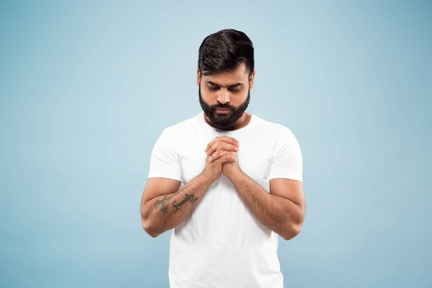 Half-length close up portrait of young hindoo man in white shirt isolated on blue wall. human emotions, facial expression, ad concept. negative space. standing and praying with eyes closed.