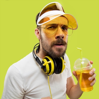Half-length close up portrait of young man in shirt. male model with headphones and drink. the human emotions, facial expression, summer, weekend concept. getting serious.