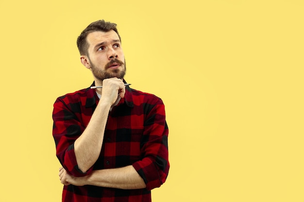 Half-length close up portrait of young man in shirt on yellow space. the human emotions, facial expression concept. front view. trendy colors. negative space