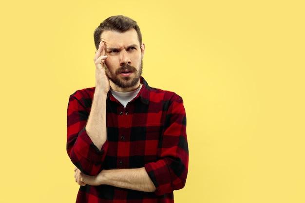 Ritratto alto vicino a mezzo busto di giovane uomo in camicia sullo spazio giallo. le emozioni umane, il concetto di espressione facciale. vista frontale. colori alla moda. spazio negativo