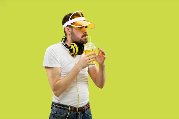 Half-length close up portrait of young man in shirt on yellow space. male model with headphones and drink