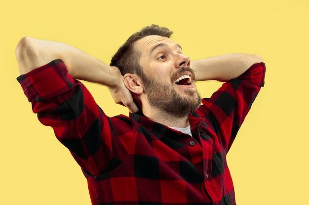 Ritratto alto vicino a mezzo busto di giovane uomo in camicia sullo spazio giallo