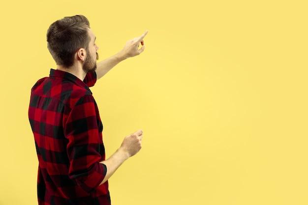 Ritratto alto vicino a mezzo busto di giovane uomo in camicia su giallo