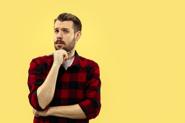 Half-length close up portrait of young man on yellow wall.