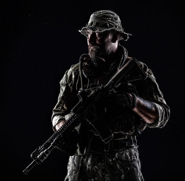 武器と制服を着たひげを生やした特殊部隊の兵士の半分の長さの輪郭のバックライトの肖像画、黒の肖像画
