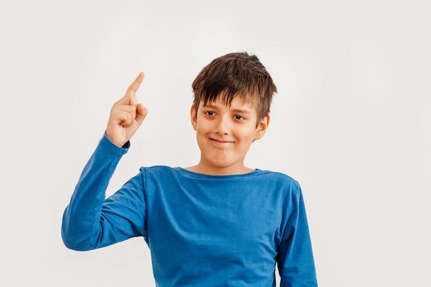 青いtシャツを着ている白人の10代の少年の半分の長さの感情的な肖像画。カメラを見て驚いたティーンエイジャー。ハンサムな幸せな子、白い背景で隔離。