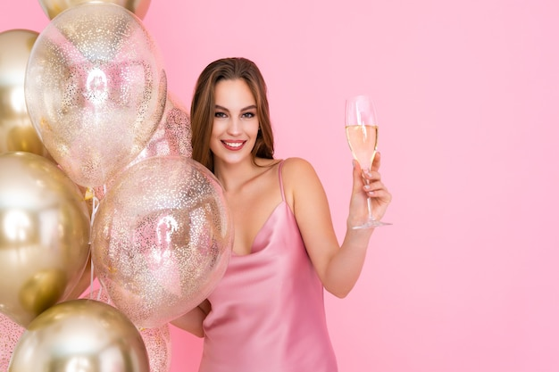 Half length of happy girl raises up glass of champagne stands near golden air balloons celebration