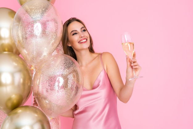 Half length of happy woman raises up glass of champagne stands near golden air balloons celebration