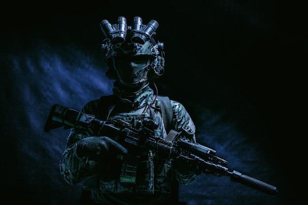 절반 길이, 육군 병사의 낮은 키 스튜디오 촬영, 마스크를 쓴 해병대원, 위장복, 현대식 탄약을 갖춘 현대식 탄약, 헬멧에 야간 투시 장치가 있는 어둠 속에 서 있는 군용 소총