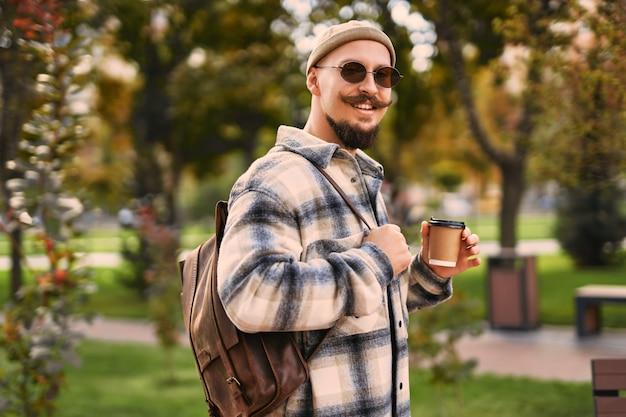 공원 야외에서 산책하는 행복한 얼굴의 절반 길이는 휴식 시간을 갖는 동안 갈 커피를 들고 있습니다