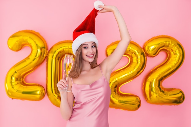 笑顔の女の子の半分の長さは、サンタの帽子の金色の気球でシャンパンのガラスを保持します新年