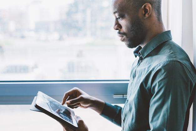 Половина длины молодой красивый бизнесмен афроамериканец у окна с табличкой