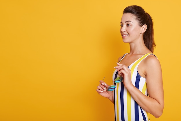 Half length photo of happy young woman with dark hair and ponitail in stylish striped swimsuit and holding sunglasses in her hands, isolated on yelow. copy space for promotion.