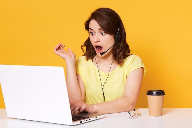 黄色で分離された画面上でノートパソコンを見て、口を開けて座っている女性オペレーターの半分の長さの写真