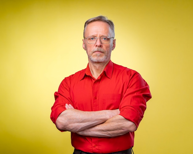 Half length picture of a mid aged business man smiling with arms crossed. solated on a yellow background