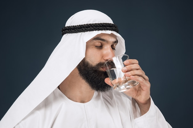 Half-length portrait of arabian saudi businessman on dark blue  space. young male model standing and drinking water