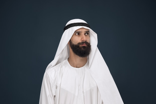 Half-length portrait of arabian saudi businessman on dark blue  space. young male model standing and looks thoughtful