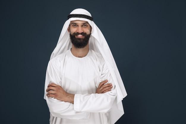 Ritratto a mezzo busto dell'uomo d'affari arabo saudita su sfondo blu scuro per studio. giovane modello maschio in piedi e sorridente. concetto di affari, finanza, espressione facciale, emozioni umane.